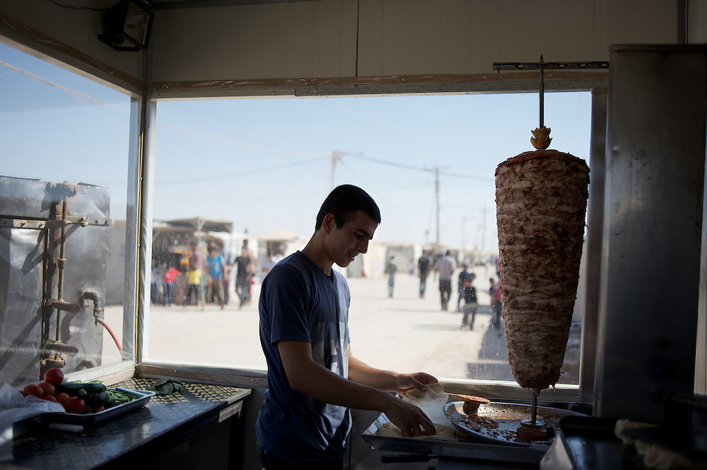August 08, 2013 - Zaatari, Jordan: A kebab vendor prepares sandwiches at his restaurant in Zaatari refugee camp, northern Jordan. The restaurant is one of many located on a street that aid workers have nicknamed the Champs Elysees, due to the hundreds of shops and businesses. Zaatari camp, home to more than 120,000 people who in the past year have fled the conflict in Syria, become the fourth largest city in Jordan and the world's second largest refugee camp behind Dadaab in eastern Kenya. Most of its residents came from Daraa, a city about 30Km away in Syria, rich with businessmen thanks to a long history of cross-border trade with Jordan. (Paulo Nunes dos Santos/Al Jazeera)
