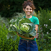 A young twenty-something woman stands in a garden, smiling and looking directly at the camera, and holding a large head of cabbage which she has just harvested. She has freckles on her face, dark hair piled on top of her head, a green tee shirt and blue jeans. In one hand is a pair of scissors which she used to cut the cabbage plant.