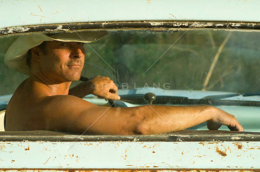 Man wearing a cowboy hat looking out the window of his Pickup truck.