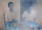partly silver mirroring vintage photograph of two Japanese boys sitting at a table
