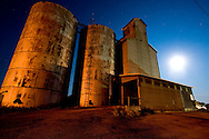 The old grain elevator at Ashkum, IL stands silent on this late night, underneath many constellations and stars overhead in the dark prairie sky. The full moon provides an extra bit of light on this night.