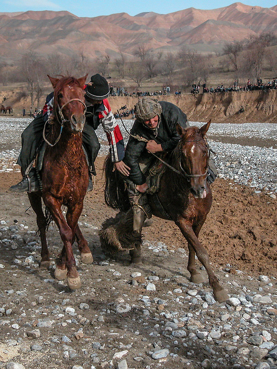 Image of Tajik horsemen fighting over the buz (a stuffed goat) while charging toward the finish at a buzkashi event in the village of Kostarosh, northwest Tajikistan