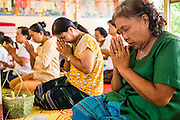 24 MAY 2013 - MAE SOT, THAILAND:    Women pray during a merit making at Wat Mae Pa in Mae Sot on Visakha Puja Day. Visakha Puja (Vesak) marks three important events in the Buddha's life: his birth, his attainment of enlightenment and his death. It is celebrated on the full moon of the sixth lunar month, usually in May on the Gregorian calendar. This year it is on May 24 in Thailand and Myanmar. It is celebrated throughout the Buddhist world and is considered one of the holiest Buddhist holidays.    PHOTO BY JACK KURTZ