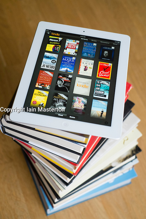iPad tablet computer with kindle e-book library application and pile of traditional hardback paper books