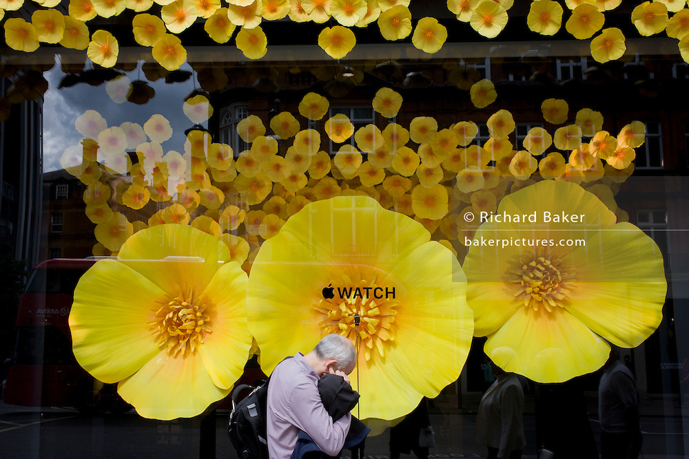 Man with finger in his ear in front of Apple Watch window display in Selfridges, central London.