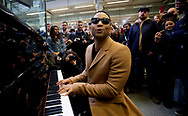John Legend plays piano and sings at King's Cross St Pancras International  Station, in central  London