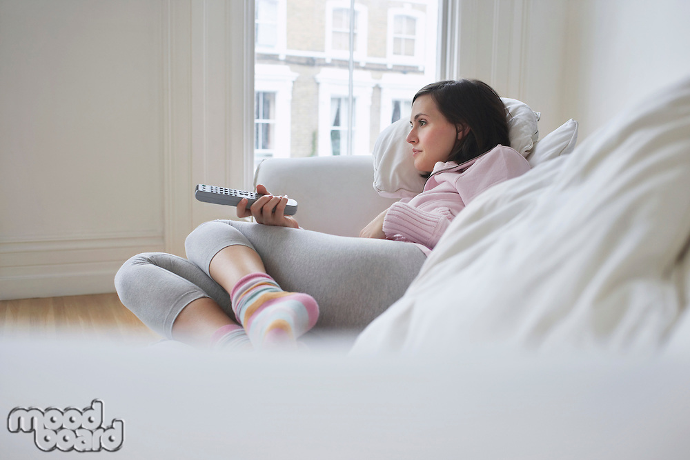 Woman lying on sofa watching television