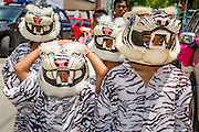 "05 JULY 2014 - BANGKOK, THAILAND: Children in tiger outfits march in a parade for vassa in Bangkok. Vassa, called ""phansa"" in Thai, marks the beginning of the three months long Buddhist rains retreat when monks and novices stay in the temple for periods of intense meditation. Vassa officially starts July 11 but temples across Bangkok are holding events to mark the holiday all week.    PHOTO BY JACK KURTZ"
