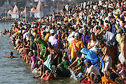 Pilgrims take their turn to bathe in the Shipra River during the Kumbh Mela festival, Ujjain, Madhya Pradesh, India. (From the book What I Eat: Around the World in 80 Diets.) The Kumbh Mela festival is a sacred Hindu pilgrimage held 4 times every 12 years, cycling between the cities of Allahabad, Nasik, Ujjain and Haridwar.  Participants of the Mela gather to cleanse themselves spiritually by bathing in the waters of India's sacred rivers.  Hindus believe that the rivers in the Indian cities of Allahabad, Haridwar, Nasik, and Ujjain are sacred, and that bathing in those rivers during the religious festival Kumbh Mela will release them from past sins and mistakes and liberate them from the cycle of birth and death. Auspicious bathing days are determined by the position of the sun and the moon, and on these days more than a million pilgrims might descend for a dip. In Ujjain, thousands of police control the crowds at the Shipra River with whistles, poles, and batons to prevent stampedes and drownings, and bathing time is kept to 12 minutes per group. Kumbh Mela is one of the largest religious festivals on earth, attracting millions from all over India and the world.  Past Melas have attracted up to 70 million visitors. The festival attracts more pilgrims than any other religious gathering on the planet, including Islam's Hajj.