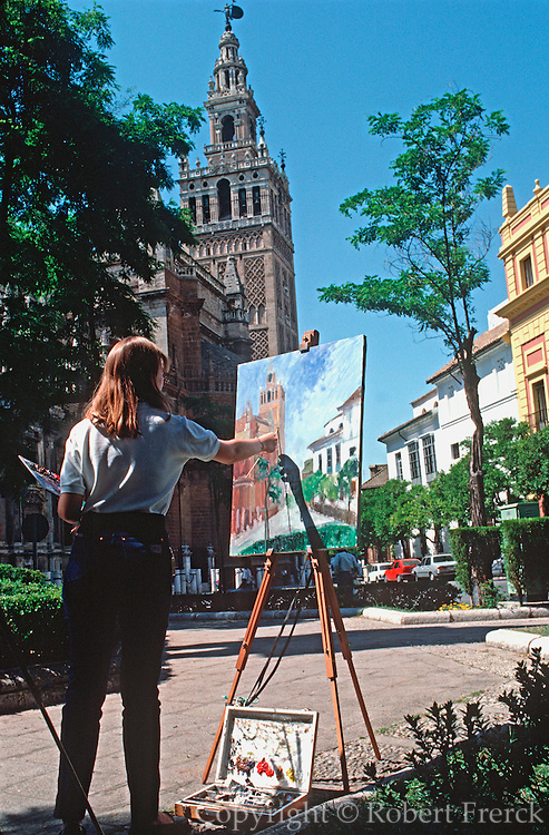 SPAIN, ANDALUSIA, SEVILLE the Cathedral and the Giralda belltower (originally Moorish tower) with painter