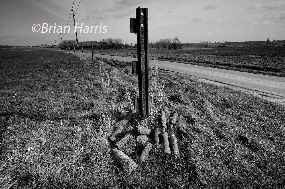Ypres-Ieper WW1 Battlefield, 1914-1918, Belgium. Unexploded WW1 Shells at Two Mine Craters, Kruisstraat, Flanders, Belgium. February 2014<br /> The Iron Harvest. Unexploded WW1 ordnance waiting to be collected by Belgian Bomb disposal team from Belgian Army in Mine Crater country to the south of Ypres. Hundreds of shells are unearthed each year on the battlefields of Flanders and across northern France.<br /> <br /> Caption information below from Wikipedia:<br /> The iron harvest is the annual &quot;harvest&quot; of unexploded ordnance, barbed wire, shrapnel, bullets and congruent trench supports collected by Belgian and French farmers after ploughing their fields. The harvest generally applies to the material from World War I, which is still found in large quantities across the former Western Front.<br /> <br /> During World War I an estimated one tonne of explosives was fired for every square metre of territory on the Western front. As many as one in every three shells fired did not detonate.[3] In the Ypres Salient, an estimated 300 million projectiles that the British and the Germans forces fired at each other during World War I were duds, and most of them have not been recovered] In 2013, 160 tonnes of munitions, from bullets to 15 inch naval gun shells, were unearthed from the areas around Ypres.[4]<br /> <br /> Unexploded weapons - in the form of shells, bullets and grenades - buried themselves on impact or were otherwise quickly swallowed in the mud. As time passes, construction work, field ploughing and natural processes bring the rusting shells to the surface. Most of the iron harvest is found during the spring planting and autumn ploughing as the region of northern France and Flanders are rich agricultural areas.[5] Farmers will collect the munitions and place them along the boundaries of fields or other collection points for authorities.<br /> <br /> Despite the condition of the shells, they remain very dangerous. The French D&eacute;partement du D&eacute;minage (Department of Mine Clearance) recovers about 900 tons of unexploded muni