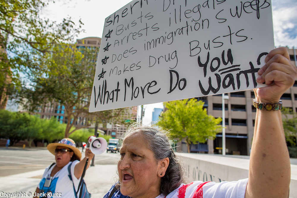 """19 JULY 2012 - PHOENIX, AZ:  MARTHA PAYAN (right under sign) speaks in support of Maricopa County Sheriff Joe Arpaio at the US Courthouse on the first day of a class action lawsuit, Melendres v. Arpaio in Phoenix Thursday. The suit, brought by the ACLU and MALDEF in federal court against Maricopa County Sheriff Joe Arpaio, alleges a wide spread pattern of racial profiling during Arpaio's """"crime suppression sweeps"""" that targeted undocumented immigrants. U.S. District Judge Murray Snow granted the case class action status opening it up to all Latinos stopped by Maricopa County Sheriff's Office deputies during the crime sweeps. The case is being heard in Judge Snow's court.  PHOTO BY JACK KURTZ"""