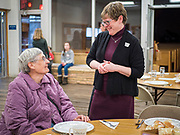 """26 FEBRUARY 2020 - FARMINGTON, MINNESOTA: Pastor KAREN EVENSON, right, talks to a diner before the community dinner at Faith Church, a United Methodist Church in Farmington, MN, about 30 minutes south of the Twin Cities. She is the minister at the church. The dinner is sponsored by Loaves & Fishes, a Christian organization that provides food for community dinners and foodbanks. Farmington, with a population of 21,000, is a farming community that has become a Twin Cities suburb. The city lost its only grocery store, a Family Fresh Market, in December, 2019. The closing turned the town into a """"food desert."""" In January, Faith Church started serving the weekly meals as a response to the store's closing. About 125 people per week attend the meal at the church, which is just a few blocks from the closed grocery store. The USDA defines food deserts as having at least 33% or 500 people of a census tract's population in an urban area living 1 mile from a large grocery store or supermarket. Grocery chains Hy-Vee and Aldi both own land in Farmington but they have not said when they plan to build or open stores in the town.      PHOTO BY JACK KURTZ"""