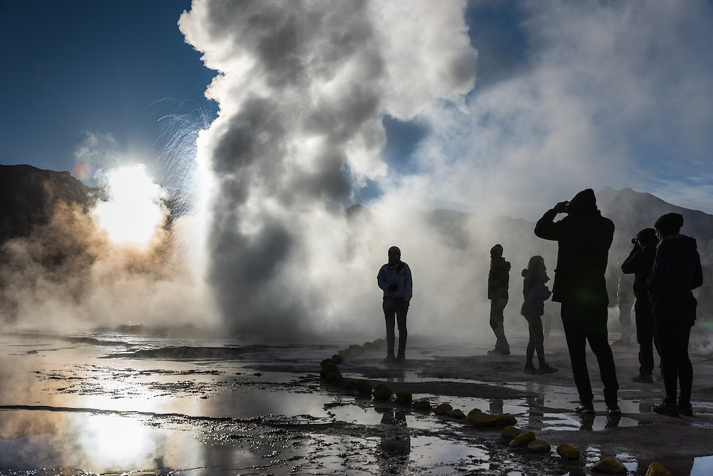 People watch in awe as the biggest geyser in the El Tatio geyser field blows out steam at sunrise. El Tatio, Chile.