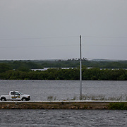 A sheriff's deputy drives along a narrow causeway Wednesday, Oct. 10, 2018 in Ozello. The low lying area has been prone to flooding in the past and most residents have already evacuated. As Hurricane Michael headed toward the Florida panhandle Cystal River residents who live along the coast expect high water during the next tide cycle.