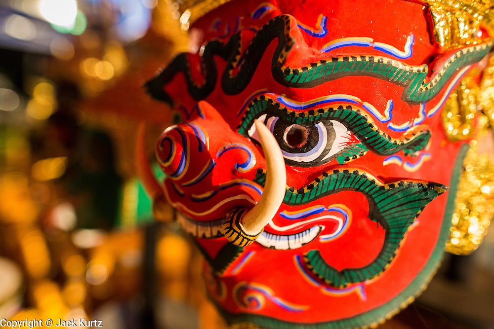 "22 NOVEMBER 2013 - BANGKOK, THAILAND:  A traditional Thai ""Khon Mask"" at a shrine performers pray at before going on stage with the Prathom Bunteung Silp mor lam troupe. Mor Lam is a traditional Lao form of song in Laos and Isan (northeast Thailand). It is sometimes compared to American country music, song usually revolve around unrequited love, mor lam and the complexities of rural life. Mor Lam shows are an important part of festivals and fairs in rural Thailand. Mor lam has become very popular in Isan migrant communities in Bangkok. Once performed by bands and singers, live performances are now spectacles, involving several singers, a dance troupe and comedians. The dancers (or hang khreuang) in particular often wear fancy costumes, and singers go through several costume changes in the course of a performance. Prathom Bunteung Silp is one of the best known Mor Lam troupes in Thailand with more than 250 performers and a total crew of almost 300 people. The troupe has been performing for more 55 years. It forms every August and performs through June then breaks for the rainy season.     PHOTO BY JACK KURTZ"