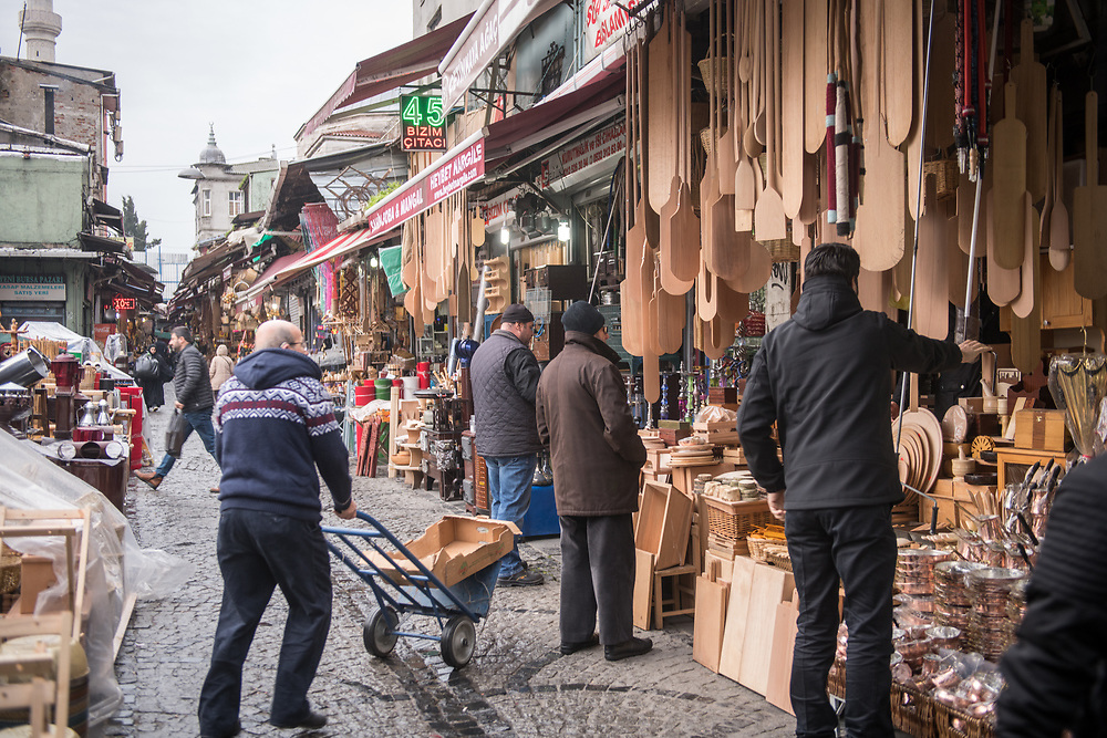 This narrow street lined with stores is busy with activity as customers browse the goods for sale outside, Istanbul, Turkey