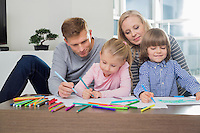 Mid adult parents with children drawing together at home