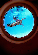 Seen through a porthole in the side of the swimming pool, two bikini-clad women swim like mermaids at Miami Beach's Art Deco, Nautical Moderne-style Albion Hotel.