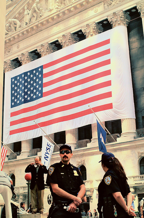 In Lower Manhattan, six days after the 9/11 terrorist attacks, New York City Police stand guard in front of the New York Stock Exchange, draped with a giant American flag; it was the first day the stock market had been open since the attacks.