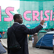 A man in a pin-striped suit is photographing the camp site. Day three of the occupation - and the first Monday. The Occupy London Stock Exchange movement was formed in London in solidarity with the US based Occupy Wall Street. The movements are a respons and in anger to what is seen by many as corporate greed and a failed banking system being bailed out by the public, - which in return are suffering austerity measures to make up for the billions of lost money. The movement occupied the St Paul's Square in the City of London Sat Oct 15 after it failed to secure and occupy Pator Noster Square and the Stock Exchnage itself.
