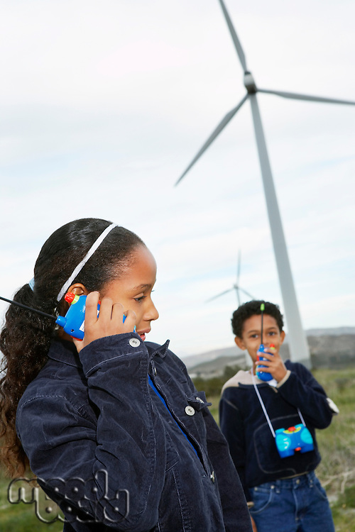 Boy and girl (7-9) playing with walky-talkies at wind farm