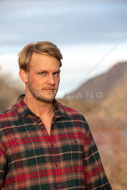 portrait of a handsome blond man outdoors at sunset