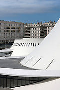 Le Volcan or the Volcano, auditorium opened 1982, designed by Oscar Niemeyer, 1907-2012, and Jean-Maur Lyonnet, at the Maison de la Culture du Havre, Le Havre, Normandy, France. Behind are apartment buildings designed by Auguste Perret, 1874-1954, who led the reconstruction of Le Havre in the 1950s, after the town was completely destroyed in WWII. The large volcano (right) contains a 1200 seat theatre and 350 seat cinema, while the small volcano (left) has a 500 seat hall and 80 seat auditorium and is now used as a reference library. The forum is built from concrete and the buildings are linked and accessed via ramps. The centre of Le Havre is listed as a UNESCO World Heritage Site. Picture by Manuel Cohen