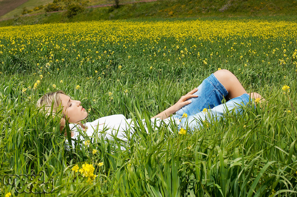 Woman sleeping in flowery meadow side view