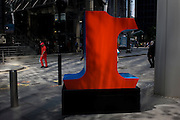 A worker in red overalls passes-by a large red number One, part of an art installation entitled 'One Through Zero (The Ten Numbers)' by American pop artist Robert Indiana (b 1928), in Lime Street, City of London, the capital's Square Mile, and its financial heart.