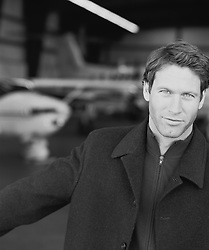 handsome man outside an airplane hanger