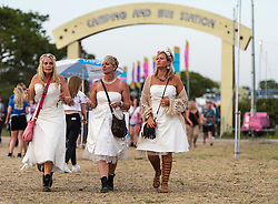 © Licensed to London News Pictures. 11/06/2015. Newport, UK.  Female festival goers wearing wedding dresses at Isle of Wight Festival 2015 celebrating a hen weekend, on thursday day 1 of the festival early evening.  Today has been hot and sunny.  This years festival include headline artists the Prodigy, Blur and Fleetwood Mac.  Photo credit : Richard Isaac/LNP