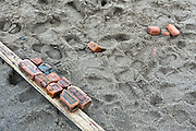 old and broken masonry bricks stacked on wood on wet beach sand