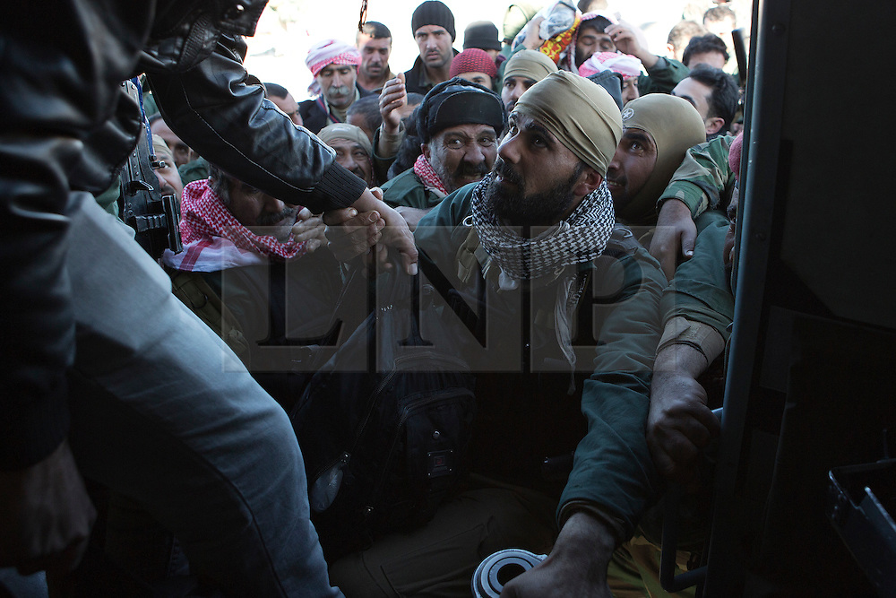© Licensed to London News Pictures. 11/12/2014. Sinjar Mountains, Iraq. Yazidi fighters jostle to get a seat to escape from Mount Sinjar on an Iraqi Air Force Mi-17 Hip helicopter during a mission to resupply trapped Yazidi refugees.<br /> <br /> Although a well publicised exodus of Yazidi refugees took place from Mount Sinjar in August 2014 many still remain on top of the 75 km long ridge-line, with estimates varying from 2000-8000 people, after a corridor kept open by Syrian-Kurdish YPG fighters collapsed during an Islamic State offensive. The mountain is now surrounded on all sides with winter closing in, the only chance of escape or supply being by Iraqi Air Force helicopters. Photo credit: Matt Cetti-Roberts/LNP