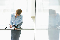 Businesswoman writing on document in office