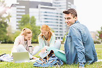 Portrait of young man with female friends studying on university campus