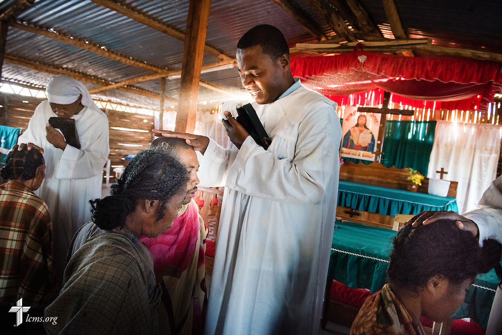 Shepherds pray for others at the Toby Mahatsinjo on Wednesday, Oct. 22, 2014, in Tsiombe, southern Madagascar. Leftover tin roofs not affixed to other Fiangonana Loterana Malagasy (FLM, Malagasy Lutheran Church) churches provided by The Lutheran Church–Missouri Synod were used to cover the roof of the Toby sanctuary. LCMS Communications/Erik M. Lunsford