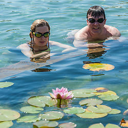 © Licensed to London News Pictures. 19/07/2016. London, UK. Office workers on their lunch break, Evelyn and Sean, enjoy the cooling waters of King's Cross pond on the hottest day of the year so far, with temperatures expected to reach 35C in the capital.  The UK's first ever man-made fresh water public bathing pond is a piece of innovative Land Art, within a working construction site area of London's King's Cross designed by Ooze architects. Photo credit : Stephen Chung/LNP