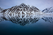 Mountain reflected in Magdalenefjorden, and 8km long, 5km wide fjord on the west coast of Spitsbergen, in the Arctic archipelego of Svalbard. Large cruise ships regularly enter the fjord. However, heavy fuel oil, which is used in many ships, is banned in Magdalenefjorden. However, Magdalenefjorden is regarded as having being sacrificed to tourism to protect other areas of Svalbard.