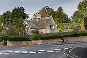 Bibury, England, UK, October 13 2018 - A young cyclist in the village.