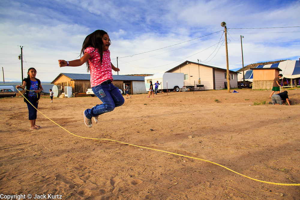 """12 JULY 2012 - FT DEFIANCE, AZ: A girl jumps rope in the children's play area at the 23rd annual Navajo Nation Camp Meeting in Ft. Defiance, north of Window Rock, AZ, on the Navajo reservation. Preachers from across the Navajo Nation, and the western US, come to Navajo Nation Camp Meeting to preach an evangelical form of Christianity. Evangelical Christians make up a growing part of the reservation - there are now more than a hundred camp meetings and tent revivals on the reservation every year. The camp meeting in Ft. Defiance draws nearly 200 people each night of its six day run. Many of the attendees convert to evangelical Christianity from traditional Navajo beliefs, Catholicism or Mormonism. """"Camp meetings"""" are a form of Protestant Christian religious services originating in Britain and once common in rural parts of the United States. People would travel a great distance to a particular site to camp out, listen to itinerant preachers, and pray. This suited the rural life, before cars and highways were common, because rural areas often lacked traditional churches.     PHOTO BY JACK KURTZ"""