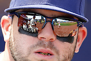 Kansas City Royals players are reflected in the sun glasses of third baseman Mike Moustakas as the team begins to take the field before a baseball game against the New York Yankees at Kauffman Stadium in Kansas City, Mo., Sunday, May 17, 2015. (AP Photo/Colin E. Braley)