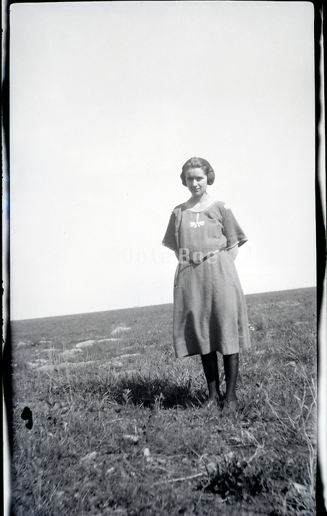 young adult woman standing hilly grass field