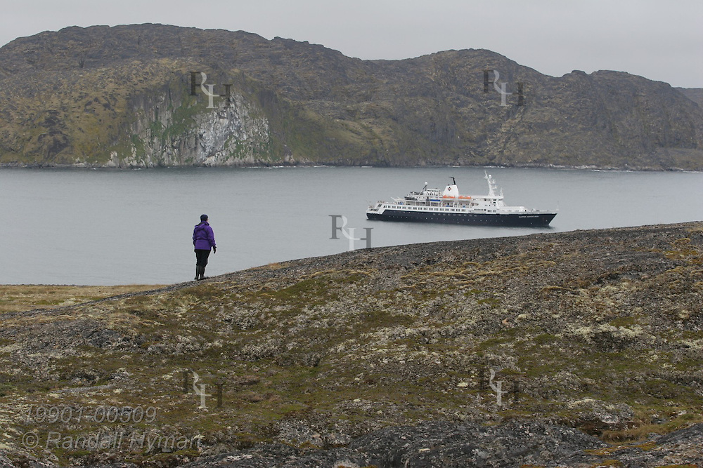 Passenger stands on ridge overlooking small expedition cruise ship, Clipper Adventurer at Eqalugssuit, Greenland