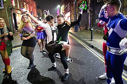© Licensed to London News Pictures . 26/12/2018. Wigan, UK. Two men dance on King Street . Revellers in Wigan enjoy Boxing Day drinks and clubbing in Wigan Wallgate . In recent years a tradition has been established in which people go out wearing fancy-dress costumes on Boxing Day night . Photo credit: Joel Goodman/LNP