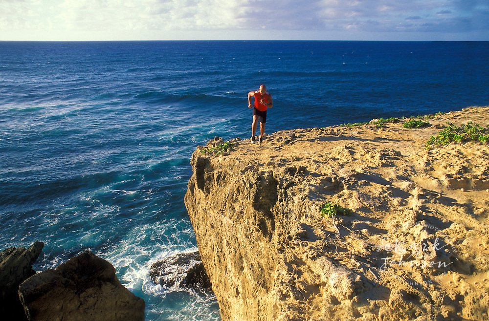 Man running along edge of seaside cliff, Kauai, Hawaii