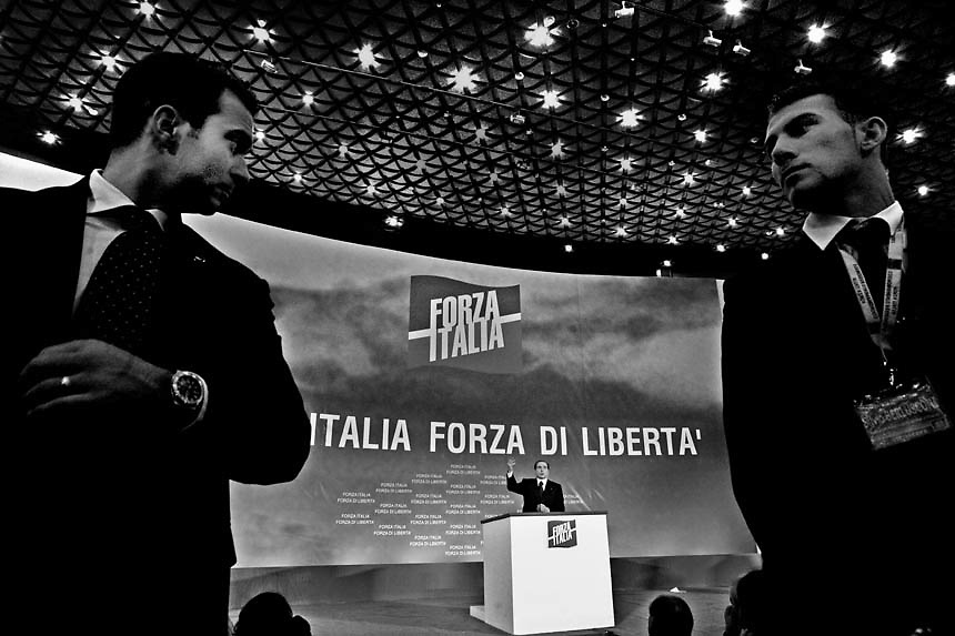 Sevurity guards spots Italian Prime Minister Silvio Berlusconi at  the PalaCongressi building in Florence, during his first electoral speech before the official opening of the italian electoral campaign. Berlusconi kicked off his re-election campaign with a rally by his party Forza Italia in Florence on Saturday.Italy's prime minister, Silvio Berlusconi, was at the centre of a political row over allegations that he was using his media empire to launch a charm offensive on the electorate in the run-up to a general election.For the past fortnight the billionaire tycoon, who owns Italy's three main private television stations, has been on a broadcasting blitz. He has given in-depth political interviews, appeared on lightweight chat shows and, on a football programme, talked about his electoral chances as well as about football.He has been a guest on state-run TV and appeared, alongside a rather startled presenter, on a radio show that broadcasts traffic news. The saturation media coverage has angered opposition politicians, who say the 69-year-old leader is trying to subvert rules meant to give balanced airtime to all political parties.