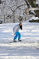 A teenager in Westchester  New York snowboards on a snowy field in her front yard. ..