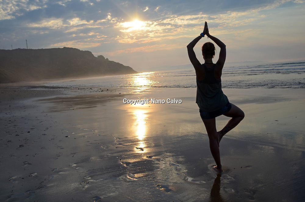 Young woman doing yoga on the beach at sunset