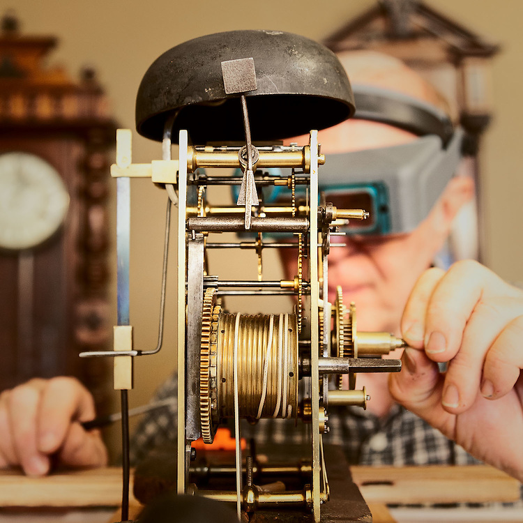 Jay Holloway, horologist at Holloway Trading, examines the internal clock mechanism.